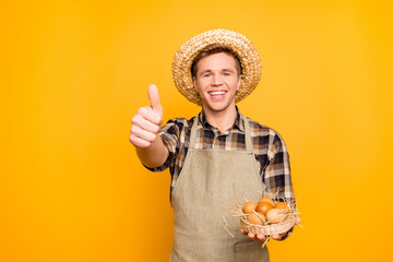 Portrait of satisfied excited hard-working delightful rejoicing handsome friendly kind farmer holding small basket with brown eggs in hand making finger up symbol isolated on bright background