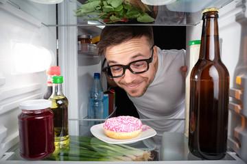 Nerd freut sich über einen Donut im Kühlschrank