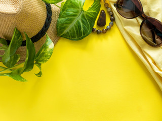 Vacation concept, summer Green leaves plant coffee Cup sunglasses bracelet hat clothes coffee on yellow background, flat lay, copy space.