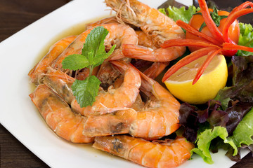 Bake shrimp with salt in white dish which has fresh vegetables decorated on dish / Select focus.