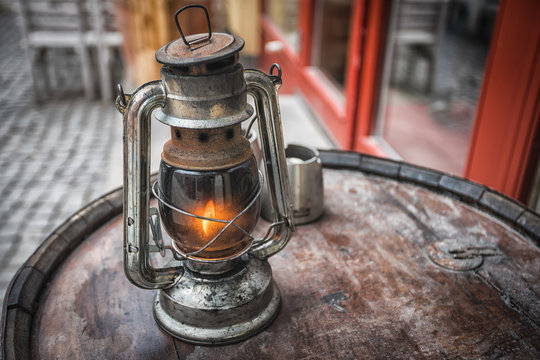 Old fashioned lantern on the wooden table. Vintage style metal lamp outdoor.
