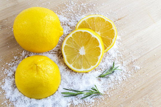 Lemon and sea salt - Beauty treatment with organic cosmetics with lemon ingredients on wood and rosemary background for body scrub and spa care.