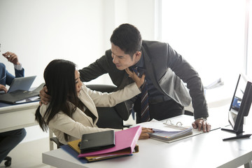 Businessman sexually harassing businesswoman colleague in office.