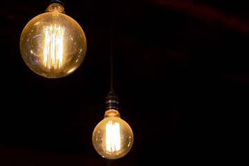 Vintage round tungsten filament bulb with dark background, technology and energy concept