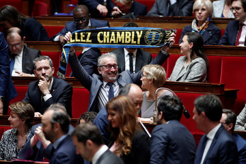 Parliament member of La Republique en Marche (Republic on the Move or LREM) political party Pascal Bois holds a scarf of the FC Chambly soccer team before the speech of Canadian Prime Minister Justin Trudeau at the National Assembly in Paris