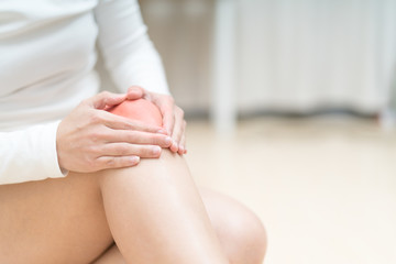 knee pain injury women sitting and touch her knee painful, healthcare and medicine concept