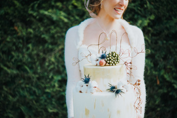 Bride with wedding cake, hedge in background