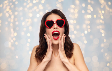 valentines day, beauty and people concept - happy smiling young woman with red lipstick and heart shaped sunglasses over holidays lights background