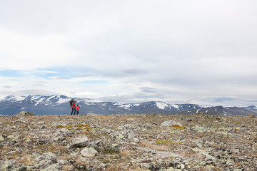 Distant view of man with sons hiking mountain landscape, Jotunheimen National Park, Lom, Oppland, Norway