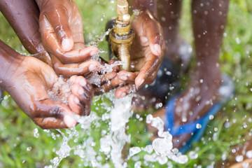 Ugandan children washing their hands at an outdoor water tap
