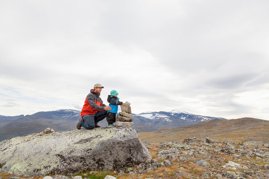 Male hiker with son building cairn in mountain landscape, Jotunheimen National Park, Lom, Oppland, Norway