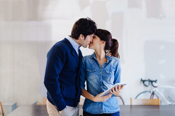 Businessman and woman in office, kissing, woman holding digital tablet