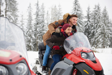 Young men riding snowmobile in winter