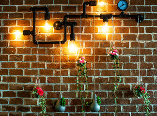 Decoration,flowers and ivy in the light bulbs hanging on metel pipe on brick wall.vintage style
