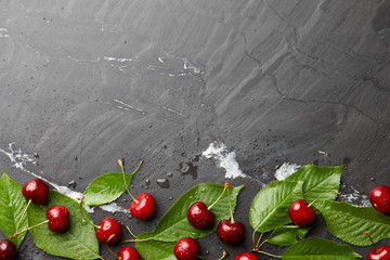 Frsh sweet cherries with leaves on black stone, top view