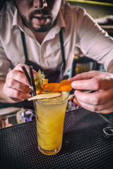 Barman is decorating cocktail