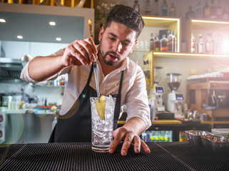 Bartender adding ginger into a glass