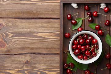 Fresh sweet cherries bowl with leaves in wooden tray, summer seasonal