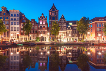 Amsterdam canal Herengracht with typical dutch houses and their reflections during morning blue hour, Holland, Netherlands.