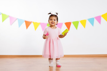 childhood, people and celebration concept - happy baby girl with toy blocks at birthday party