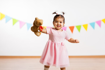 childhood, people and celebration concept - happy baby girl with teddy bear toy on birthday party