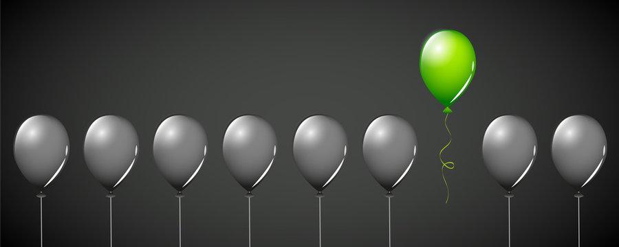 ein grüner luftballon unter vielen schwarzen