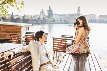Elegant brunet young male in white formal costume poses at camera while has rest at wooden bench and admires wonderful view in front. Pretty woman uses professional camera for making photos.