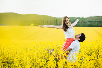 Romantic man raises his girlfriend, enjoy togetherness at beautiful yellow field, pose outdoor, have fun, smile joyfully. Couple in love spend summer holidays at nature. People and harmony concept