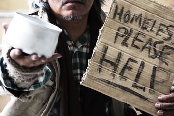 Lifestyle Homeless man on walkway street in capital city.