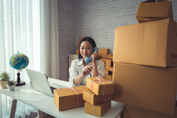 Young woman small business owner online shopping at home. confirm orders from customers with mobile phones preparing package product on background. SME entrepreneur or freelance life style concept.