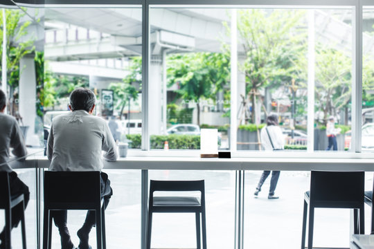 man sitting in coffee shop by the window in the morning