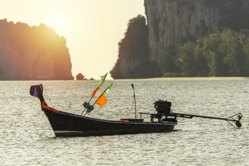 old fishing tail boat in the sunset sea with island at background