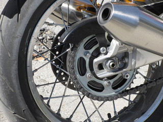 Rear wheel and chromed exhaust pipe of a classic motorcycle . Side view