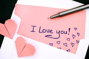 Letter with text I Love You! in envelope with two pink origami hearts and pen.