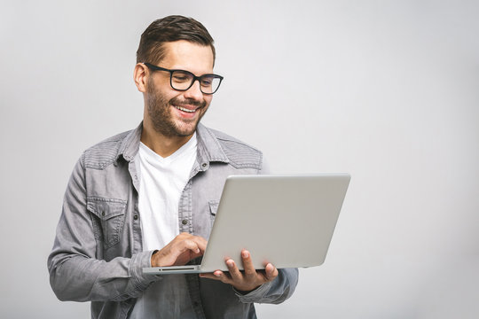 Confident business expert. Confident young handsome man in shirt holding laptop and smiling while standing against white background