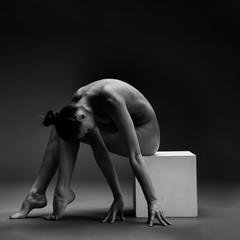 Naked woman. Nude girl doing yoga. Gymnastic exercises. Female beauty of a body.