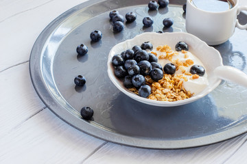 Healthy breakfast of granola with blueberries and yogurt and cup of coffee on a tray