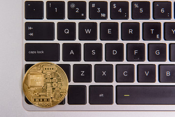Cryptocurrency physical golden bitcoin coin on keyboard