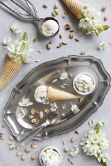 Close-up photo of fresh ice-cream on metal tray with white flowers and nuts