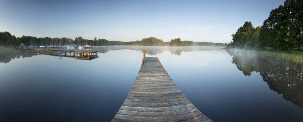 Calm lake reflections with jetty, boats and nature on summer morning in north Poland. Bobiencino lake in pomerania.