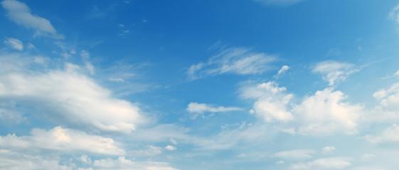 Light cumulus clouds in blue sky. Wide photo.