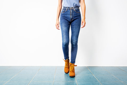 Young girl blue jeans brown shoes wall white.