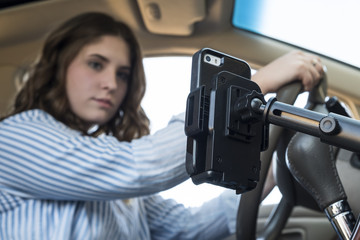 Young woman driving a car and looking at her cellphone