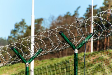 Fence with razor barbed wire. Guarded area. Military base. Razor wire.