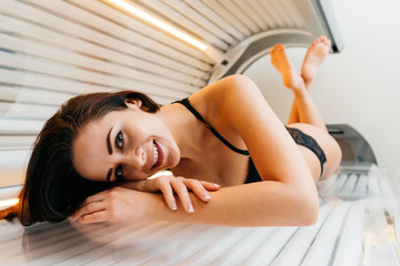 happy attractive girl in black bathing suit sunbathing in horizontal sunbed and smiling