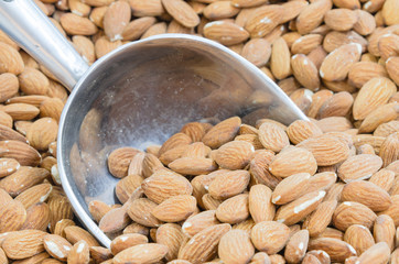 Background pile of organic dried almond bulk sale at local market in America. Full frame view of raw almonds with metal scoop, healthy nut