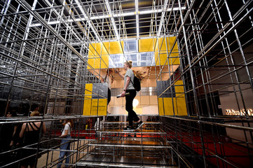 A woman takes a picture at an installation during the Milan Design Week