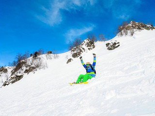 Photo of young man in helmet and with snowboard lying on mountain slope