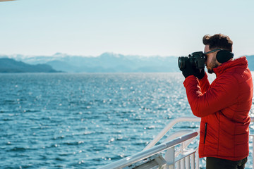 Picture of a young caucasian man taking photo of a beautiful landscape on his professional camera. Photographer taking picture of the sea. Stavanger, Lysefjord, Norway. Side view