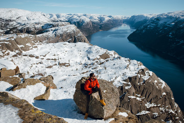 Top view of caucasian traveler man in red jacket sitting on a cliff and enjoying the scenic view of the mountains and lake. Preikestolen, Pulpit rock, Lysefjord, Norway